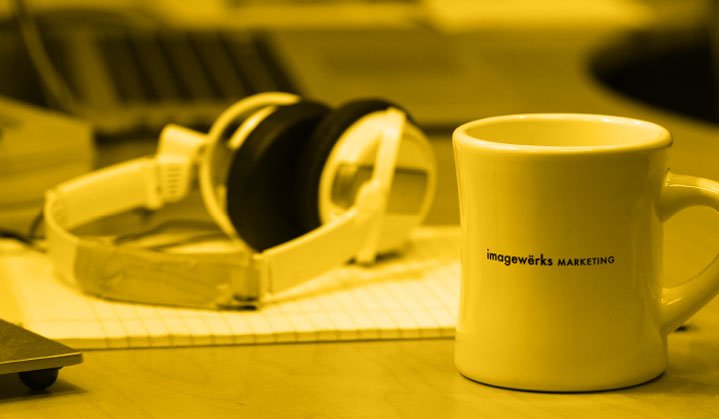 Candid shot of a desk with IWM coffee mug and headphones