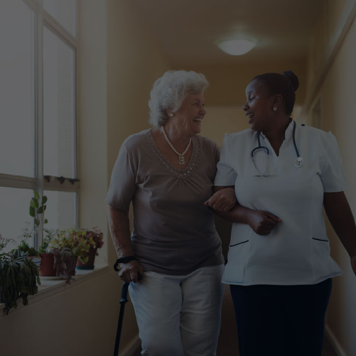 Nurse helping elderly woman walk the hall